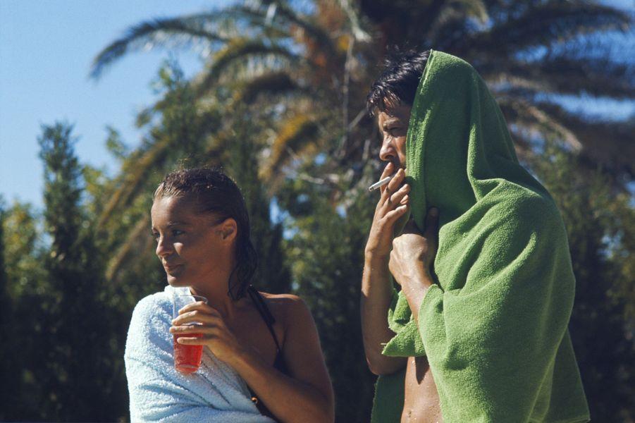 """Tournage du film """"La piscine"""" de Jacques DERAY dans le décor d'une somptueuse villa aux environs de Saint-Tropez pourvue d'une immense piscine : plan de trois-quarts de Romy SCHNEIDER un verre à la main aux côtés d'Alain DELON fumant une cigarette, tous deux enroulés dans une serviette lors d'une pause."""