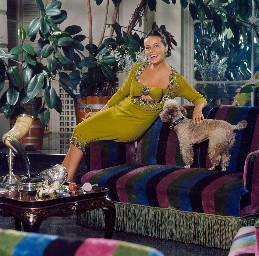 Jeanne Moreau assise sur un canapé chez son compagnon Pierre Cardin, habillée d'une robe verte, présentant la mode Cardin 1964.