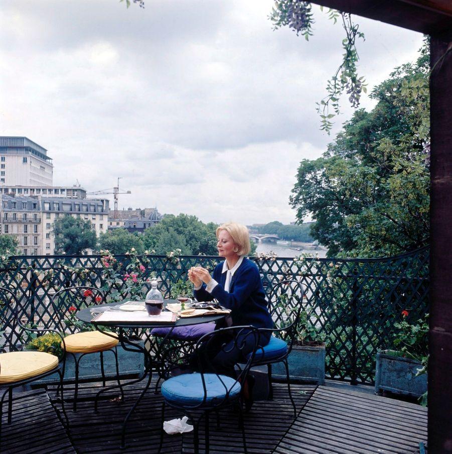 Michèle Morgan, déjeunant sur la terrasse de son appartement de l'île Saint-Louis.