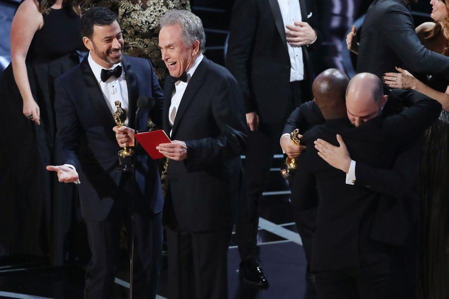 """Jimmy Kimmel ne comprend pas, pendant qu'un producteur de """"La La Land"""" tombe dans les bras d'un producteur de """"Moonlight"""" incrédule."""