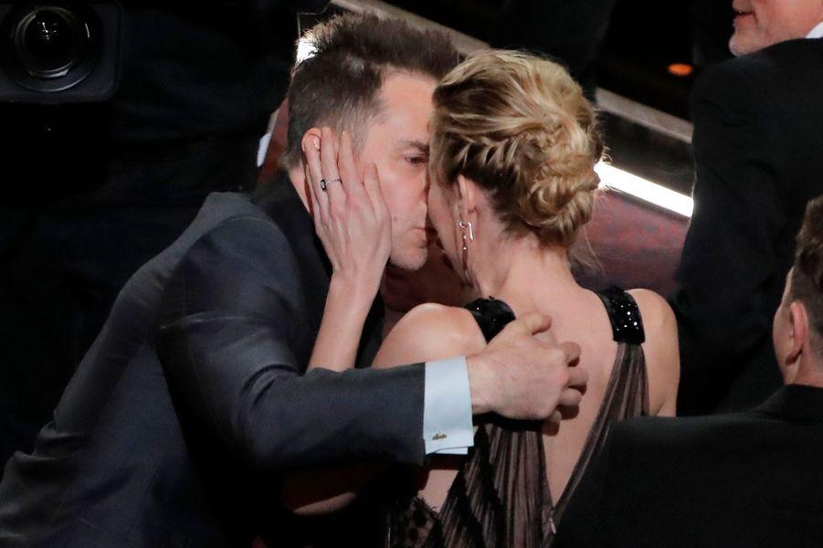 Sam Rockwell embrasse sa compagne avant de monter sur scène pour l'Oscar du meilleur second rôle.