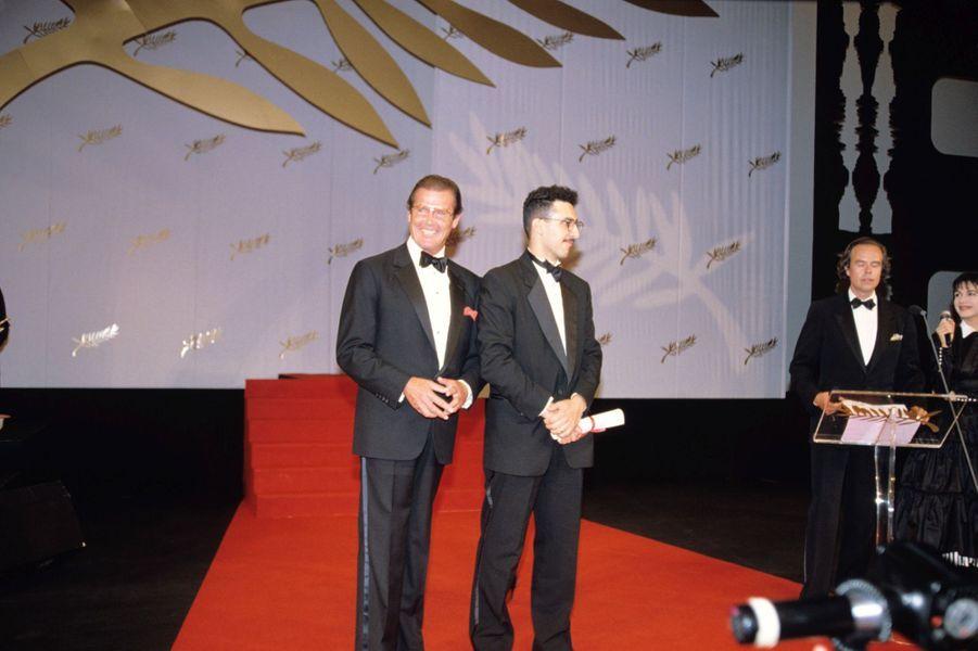 Festival Cannes 1991, l'immense Roger Moore remet le prix d'interprétation masculine àJohn Turturro,pour son rôle dans «Barton Fink» des frères Coen.