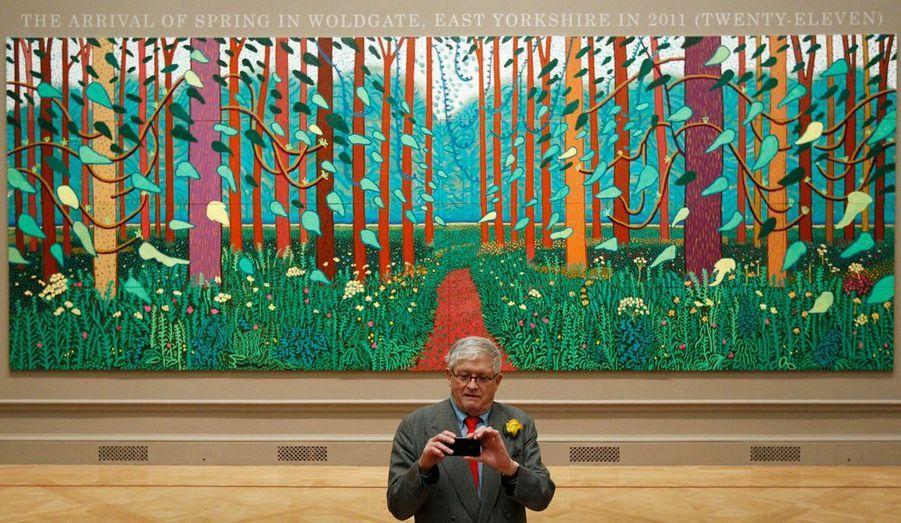"""Le peintre anglais David Hockney pose devant la toile """"The Arrival of Spring in Woldgate, East Yorkshire in 2011 (twenty-eleven)"""" à la Royal Academy of Arts de Londres, le 16 janvier 2012. The Royal Academy exposera des toiles de David Hockney du 21 janvier au 9 avril."""