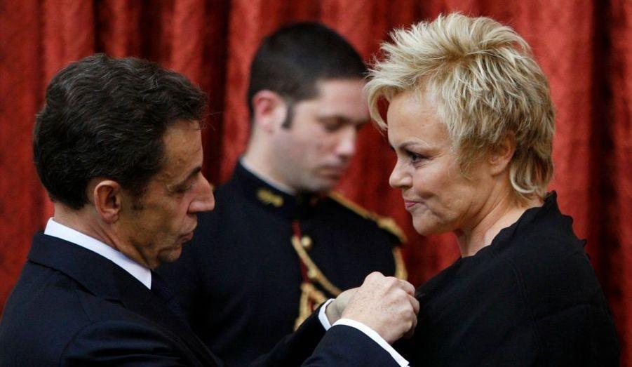 """Muriel Robin recevant la Légion d'honneur, mercredi à Paris des mains de Nicolas Sarkozy. Le président de la République a salué le """"talent"""" de l'humoriste qu'il a qualifié de """"populaire sans être populiste"""", qui amène """"à réfléchir, sans jamais donner de leçons"""".""""On a envie de vous admirer, de vous protéger. La République s'honore en distinguant quelqu'un qui est à ce point humain"""", a-t-il ajouté."""