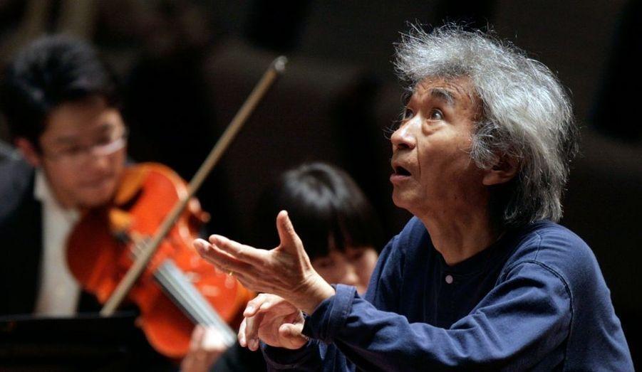 """Le Japonais Seiji Ozawa (ici au Théâtre National de Pékin, en 2009) a fait dimanche soir son retour à la direction d'orchestre après avoir lutté pendant neuf mois contre un cancer de l'oesophage. Considéré comme l'un des plus brillants chefs d'orchestre de sa génération, Ozawa, 75 ans, est venu ouvrir le Festival Saito Kinen de Matsumoto, dans le centre du Japon. Il a été accueilli par un tonnerre d'applaudissements, auxquels il a répondu en expliquant qu'il était de retour mais souffrait à présent du dos. """"Permettez de vous présenter mes excuses aujourd'hui. J'ai été soigné par des docteurs magnifiques donc je peux dire que j'ai passé mon épreuve de malade du cancer, mais il y a un petit hic - mon dos, qui m'a causé des problèmes par le passé, va de nouveau mal"""", a-t-il dit au public."""