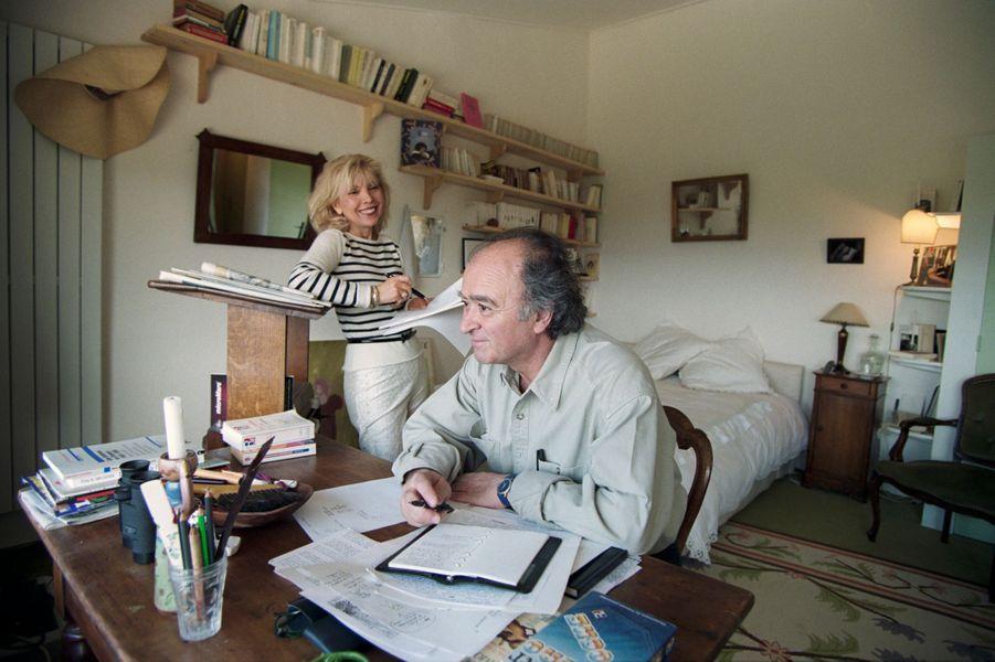Georges WOLINSKI dans sa chambre, installé à son bureau. Son épouse Maryse se tient auprès de lui