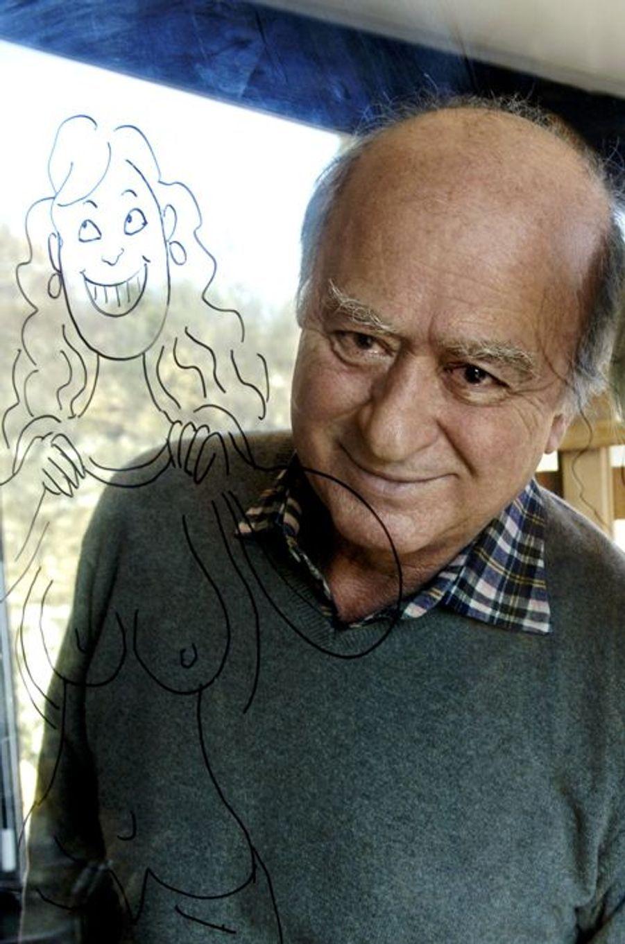 Georges WOLINSKI derrière une vitre en transparence sur laquelle une jolie fille de la main de Wolinski exhibe sa poitrine.