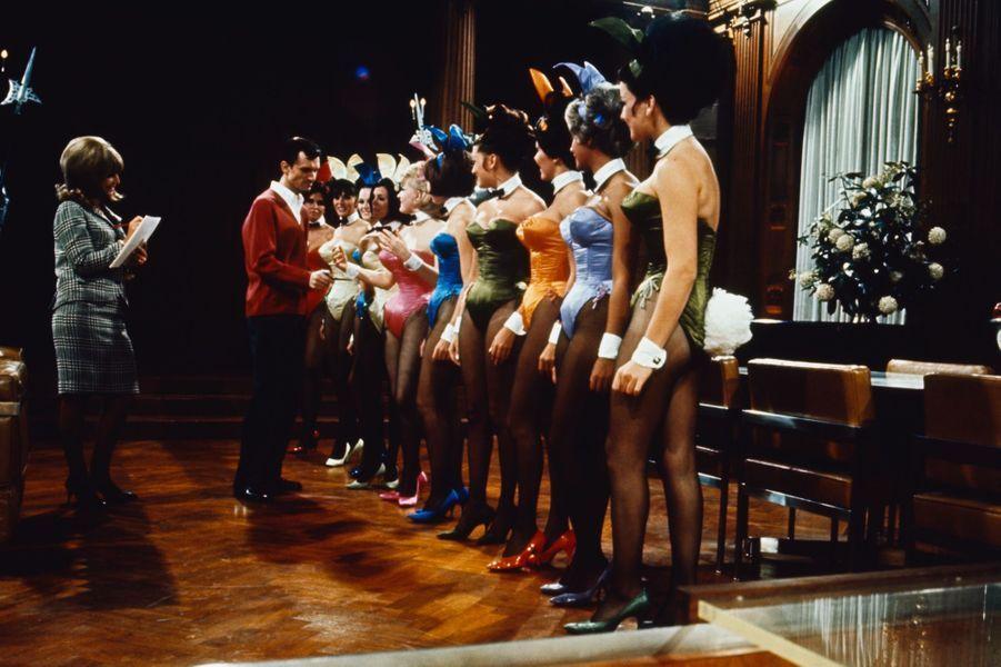 Dans son bureau de Chicago, Hugh Hefner observe ses playmates et leurs nouveaux costumes.