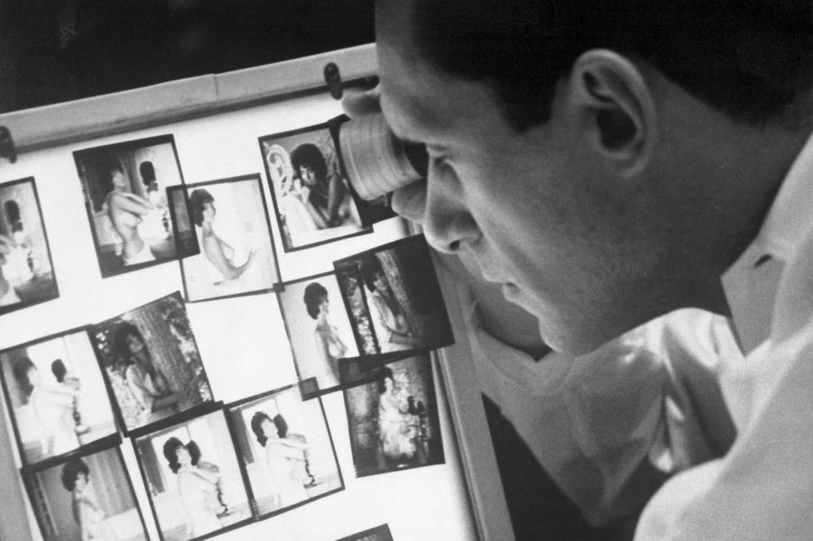 Au travail, Hugh Hefner analyse les photos prises pour son magazine.