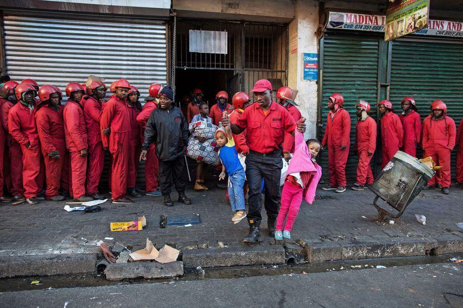 Un chef d'équipe traîne deux enfants dehors lors de l'expulsion d'un bâtiment occupé illégalement. Bree Street, Johannesburg, 23 juin 2017.Visa d'or Région Occitanie - Pyrénées-Méditerrannée