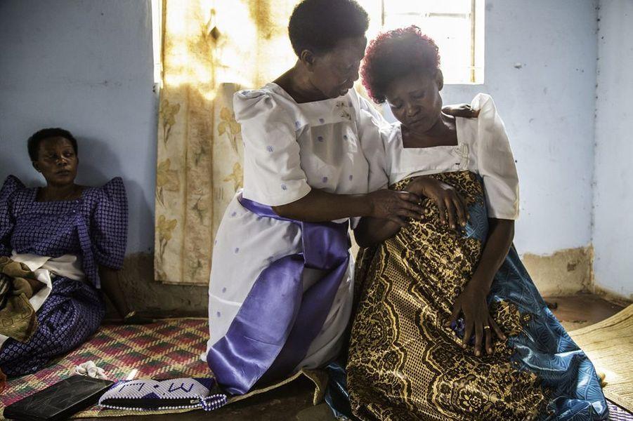 Des responsables de l'église locale accueillent Solome Sekimuli (54 ans), dont le mari diabétique, Ben, est décédé la semaine précédente. Solome avait 17 ans et Ben 19 ans lorsqu'ils se sont mariés. Ses beaux-frères l'ont chassée de la maison. District de Luweero, Ouganda, 13 juin 2016.