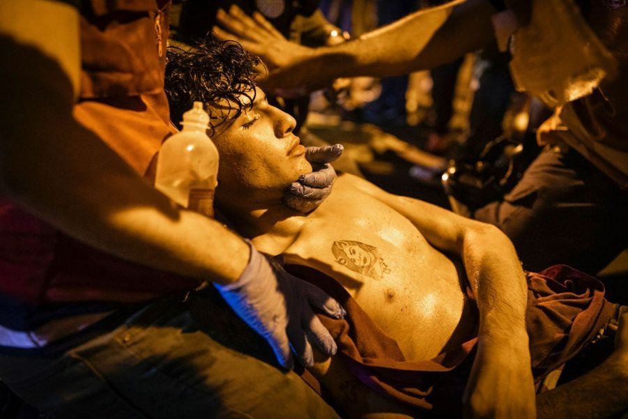 """""""SEUL DIEU PEUT ME JUGER"""" - IRAK 2018-2019 Un jeune homme est traité pour les effets des gaz lacrymogènes lors d'affrontements entre des manifestants anti-gouvernementaux et les forces de sécurité irakiennes à Bagdad."""
