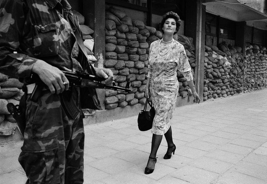 """EXTRAORDINARY WOMENTWomen Of SarajevoSarajevo, 1995. Dans la banlieue dangereuse de Dobrinja, Meliha Vareshanovic marche fièrement avec un air de défi pour aller travailler pendant le siège de Sarajevo. Son message aux hommes armés qui veillent autour de sa ville est simple: """"Vous ne nous battrez jamais""""."""