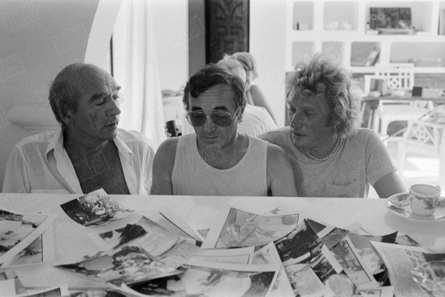 Charles Aznavour entouré d'Eddie Barclay et Johnny Hallyday, dans la fameuse villa du producteur à Ramatuelle, près de Saint-Tropez, en août 1980.