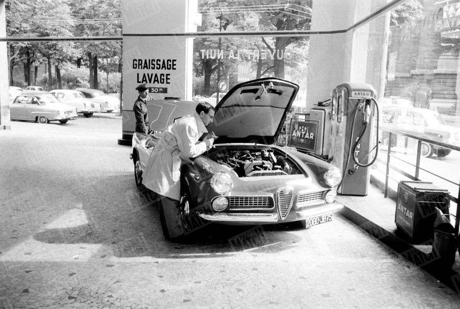 Charles Aznavour, en route pour l'ouverture du 46e Salon de l'automobile, vérifie le moteur sa voiture, une Alfa Romeo 2000 Spider, le 17 septembre 1959.