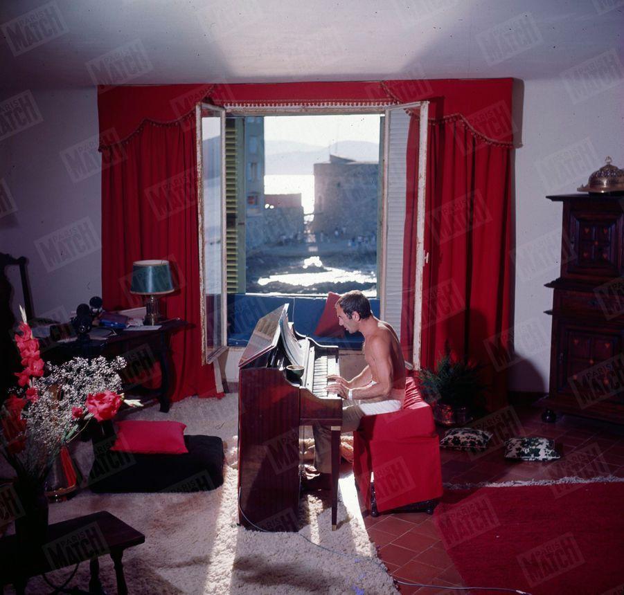 Charles Aznavour joue du piano dans sa maison de Saint-Tropez en juin 1964.