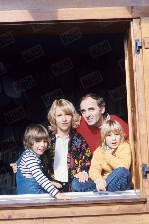 Charles Aznavour son épouse Ulla et leurs enfants Misha, âgé de 5 ans et Katia, âgée de 8 ans, à la fenêtre de leur maison en Suisse, en novembre 1977.