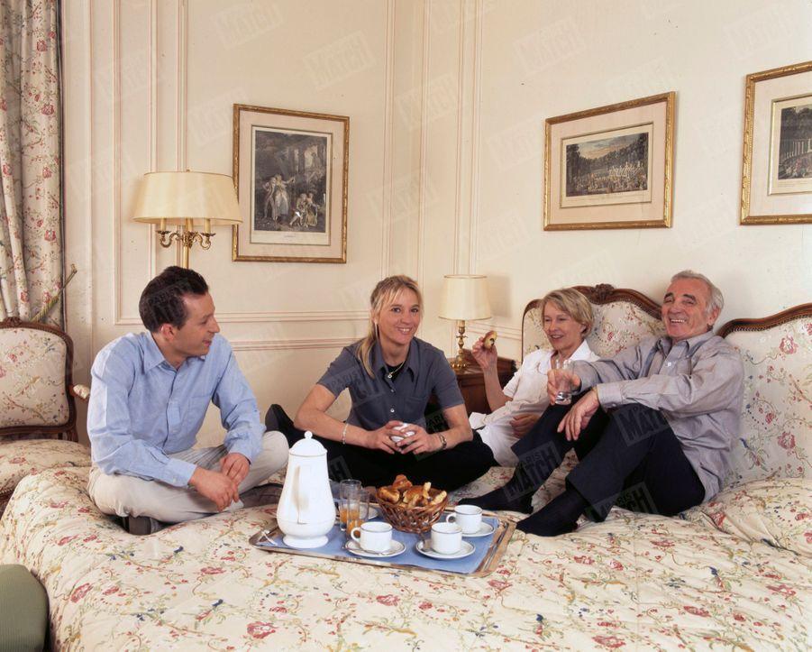 A Versailles, à l'hôtel Trianon Palace, dans une chambre d'hôtel, Charles Aznavour, entouré de sa femme Ulla, de son fils Misha, et de sa fille Katia, le 9 avril 1999.