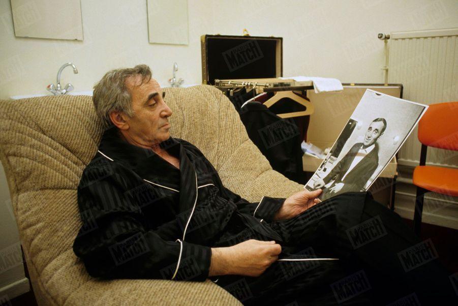 Charles Aznavour dans sa loge à l'occasion d'un concert à Dunkerque, regardant une photographie de lui-même, le 10 décembre 1987.
