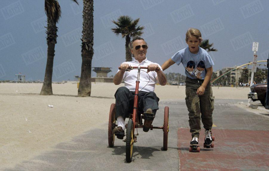 Charles Aznavour fait du tricycle sur la promenade de Santa Monica, en Californie, au bord de la plage, avec son fils Nicolas (11 ans) l'accompagnant en patins à roulettes, le 7 juillet 1987.