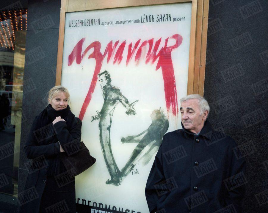 """Charles Aznavour avec sa fille Katia posant, le 8 novembre 1998, de chaque côté de l'affiche annonçant la série de concerts que le chanteur donne dans la salle du """"Marquis"""", à Broadway, New York"""