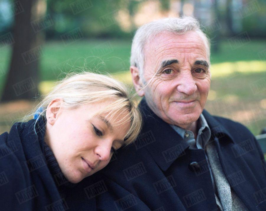 """Charles Aznavour avec sa fille Katia posant, le 8 novembre 1998, sur un banc de Central Park à l'occasion d'une série de concerts que le chanteur donne dans la salle du """"Marquis"""", à Broadway, New York."""