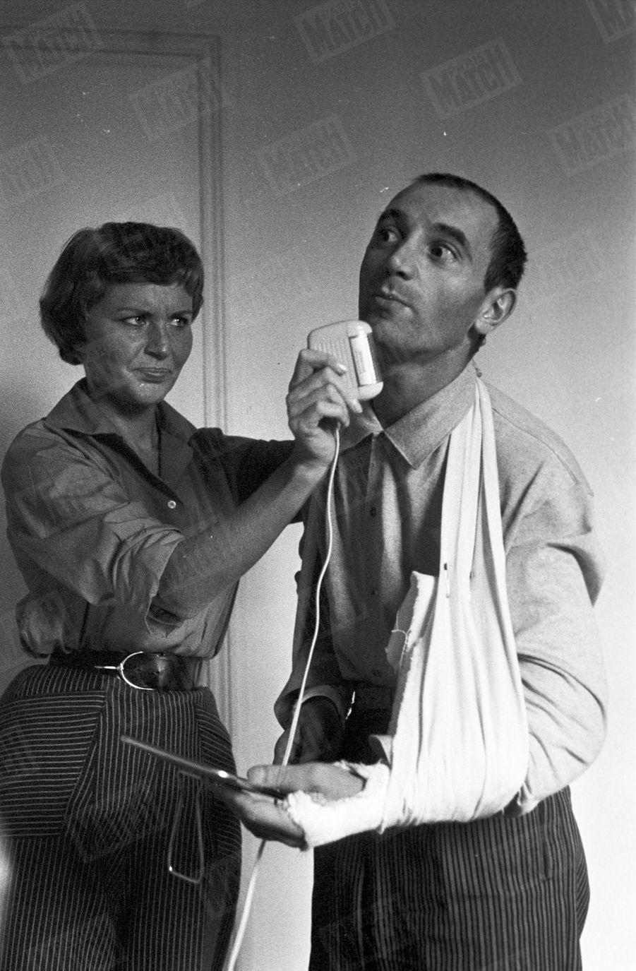 Pour sa toute première photo dans Match, Charles Aznavour, les deux bras plâtrés après un accident de voiture, se fait raser par son épouse Evelyne Plessis, le 4 octobre 1956.