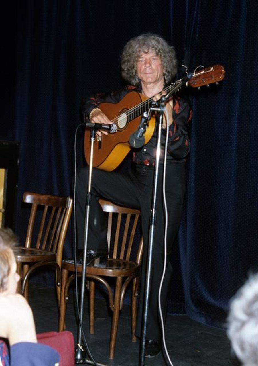 Portrait de Manitas DE PLATA sur scène une guitare dans les mains, un pied sur une chaise, en 1983