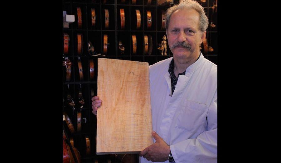 Bernard Sabatier dans son coffre, où il conserve ses plus belles trouvailles. Il tient ici un morceau de peuplier du Jura, sur lequel il a dessiné son prochain violon.