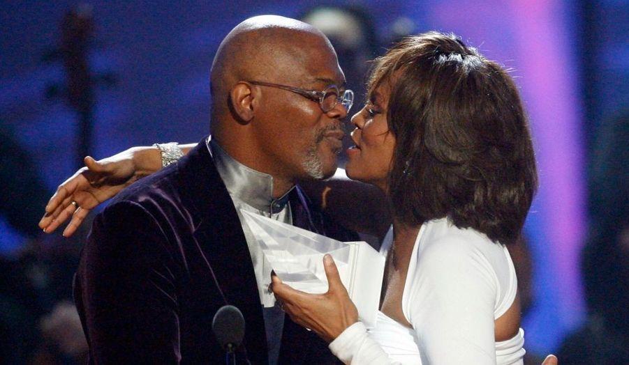 Whitney Houston embrassant le présentateur des 35e American Music Awards, Samuel L. Jackson, après avoir reçu le prix de la Meilleure artiste internationale, hier soir à Los Angeles.