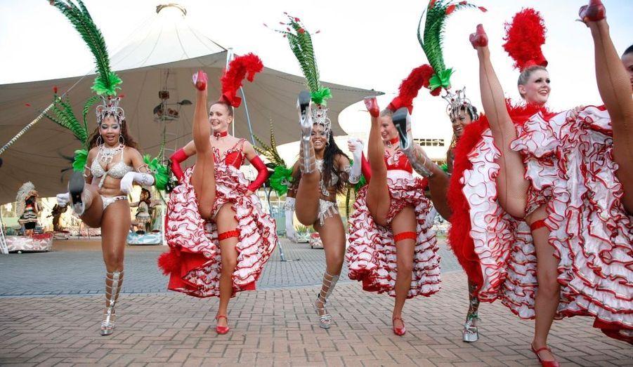 Sur la grand-place de «La Cité de la samba», trois danseuses du Moulin initient trois sambistes aux secrets du french cancan.
