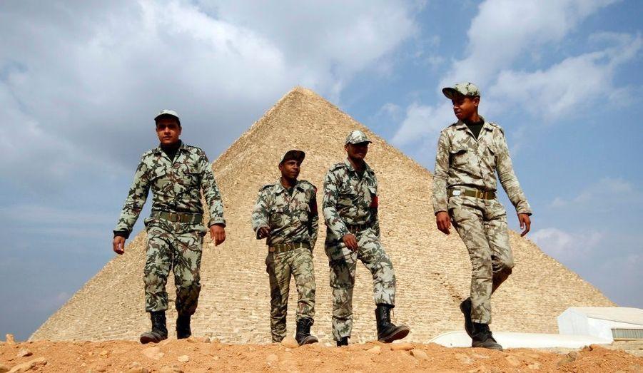 Des soldats égyptiens marchent près des pyramides de Gizeh, vidées des touristes. Depuis deux semaines, des milliers d'Egyptiens se retrouvent sur la place Tahrir du Caire pour réclamer le départ du président Hosni Moubarak.