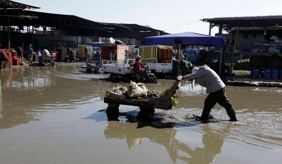 Un homme pousse son chariot sur le parking d'un supermarché, à Bagdad, en Irak. Les fortes pluies qui se sont abattues sur la ville ces derniers jours ont provoqué d'importantes inondations.