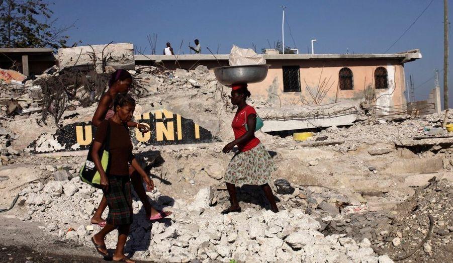 Des Haïtiens marchent entre les débris causés par le séisme à Port-au-Prince.