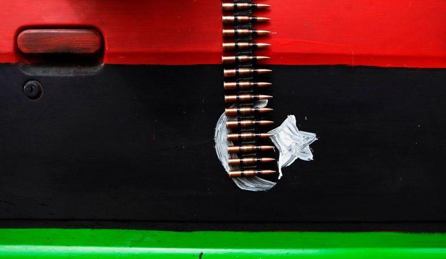 Une ceinture de munitions, dépassant de la portière d'un véhicule peint aux couleurs des insurgés libyens, à proximité de Brega.