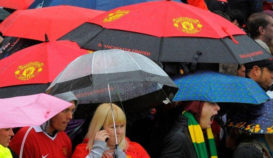 Des supporters de l'équipe de football Manchester United attendent le passage du bus transportant les joueurs du club pour fêter leur titre de champion d'Angleterre. Une parade qui devrait remonter le moral aux hommes de Sir Alex Ferguson, battus samedi en finale de la Ligue des Champions par les Catalans du FC Barcelone (3-1).