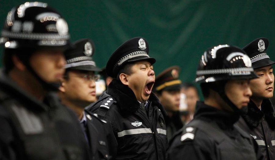 Ce policier chinois baille alors qu'il encadre une campagne contre la production et la distribution de films pornographiques et piratés, à Pékin.