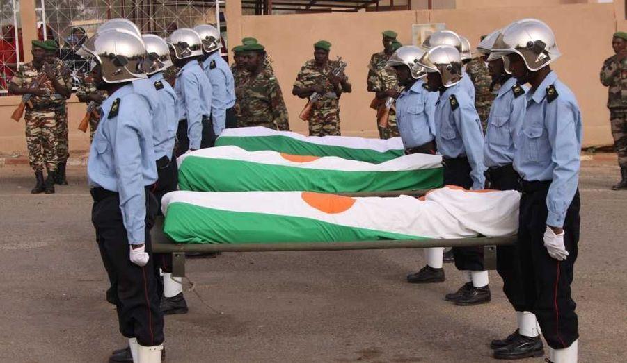 Les corps des gendarmes tués dans l'opération échouée de libération des deux jeunes Français samedi à Niamey, sont recouverts du drapeau national, lors d'une cérémonie leur rendant hommage, dans la capitale nigérienne, en présence d'Alain Juppé.