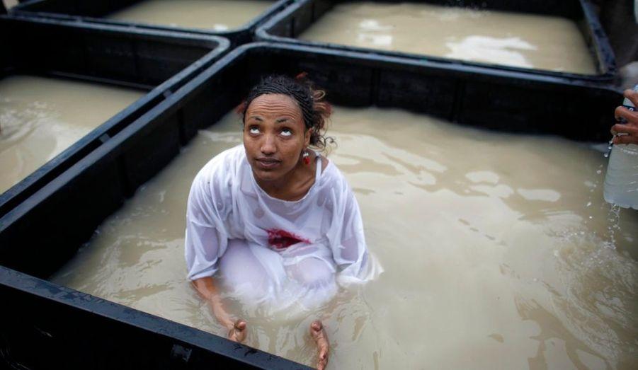 Une jeune femme chrétienne est plongée dans l'eau du Jourdain lors d'un pèlerinage près de la ville de Jéricho, en Cisjordanie. Les chrétiens orthodoxes ont afflué vers le fleuve pour célébrer la fête de l'Epiphanie, sur le site où Jean-Baptiste aurait baptisé Jésus Christ.