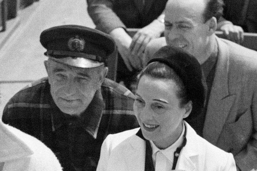 Festival de Cannes, 1953 : Arletty assise à côte de l'acteur Charles Vanel à bord d'un bateau.