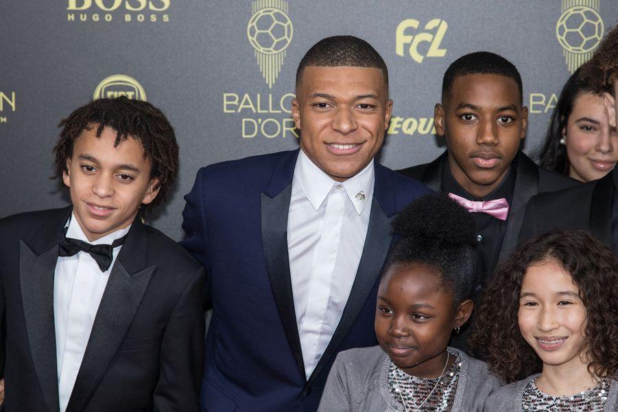 Kylian Mbappé et son petit frère Ethan (à gauche) avec les enfants de l'association Premiers de cordéeà la cérémonie du Ballon d'Or 2019 à Paris le 2 décembre 2019