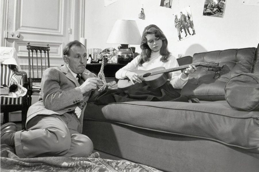 """1952 : Brigitte Bardot, partenaire de Bourvil dans le film """"Le Trou Normand"""", lui joue de la guitare."""