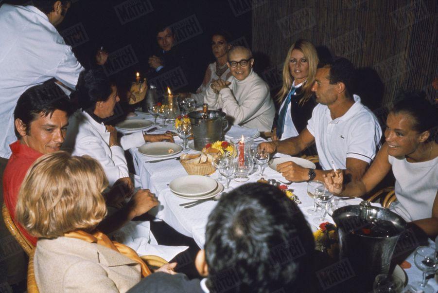 Brigitte Bardot, Romy Schneider, Alain Delon, Eric Tabarly, Maurice Roney et des amis dînentà Saint-Tropez, à la fin du mois d'août 1968.