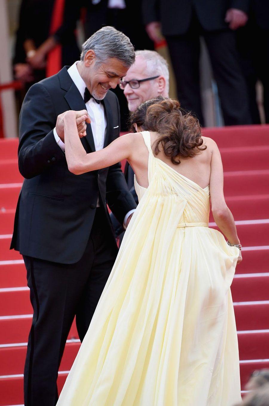 George Clooney aide sa femme à monter les marches du Palais des Festivals