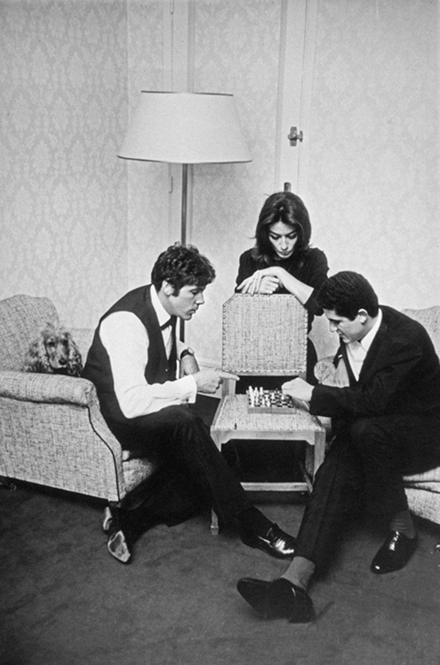 Claude Lelouch joue aux échecs avec Pierre Barouch dans une chambre d'hôtel sous le regard d'Anouk Aimée, mai 1966