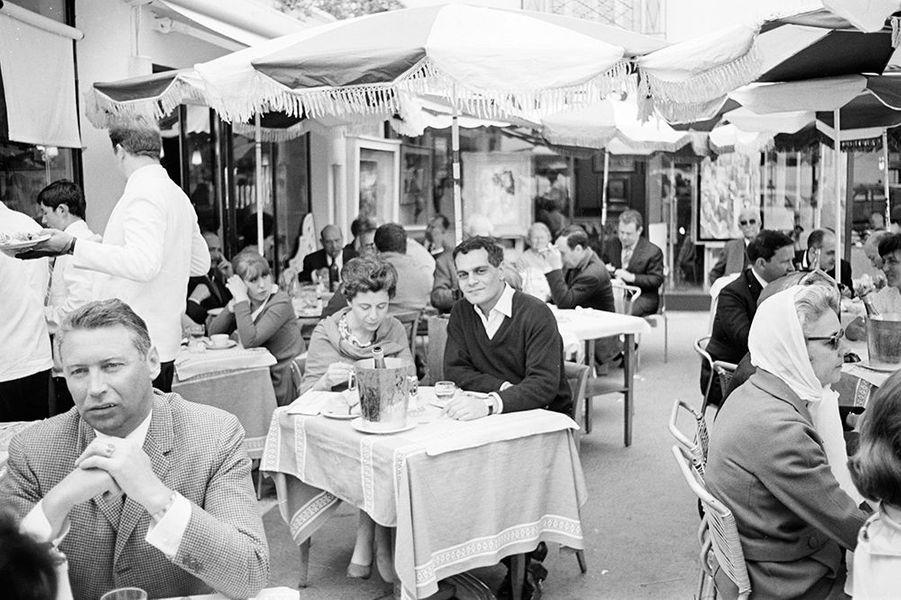 Omar Sharif déjeune à la terrasse d'un restaurant à Cannes, mai 1966