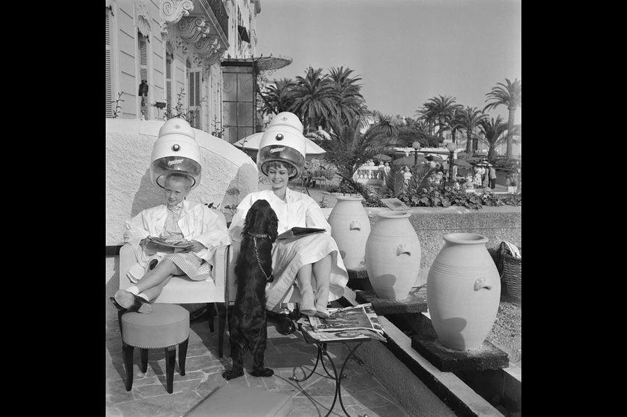 """Le 8ème Festival de CANNES se déroule du 26 avril au 10 mai 1955. Les deux Brigitte de Cannes : Brigitte FOSSEY (8 ans et demi) et Brigitte BARDOT (20 ans) ont fait connaissance chez le coiffeur. La seconde est accompagnée de """"Clown"""", son cocker."""