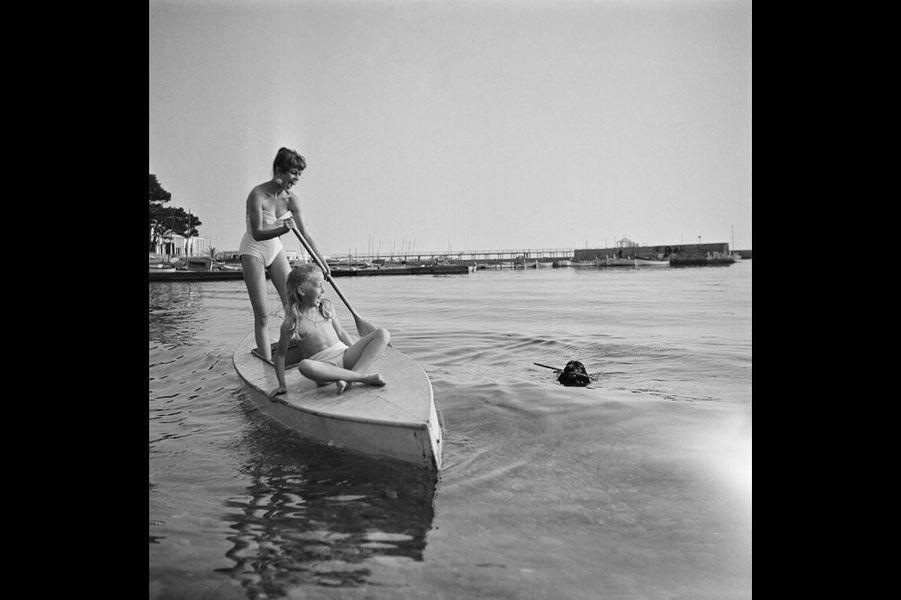 """Le 8ème Festival de CANNES se déroule du 26 avril au 10 mai 1955 : attitude riante de Brigitte BARDOT (20 ans) et Brigitte FOSSEY (8 ans et demi) sur une sorte de barque, BB debout une rame à la main tandis que son chien cocker, """"Clown"""" revient vers elles à la nage, un baton dans la gueule."""