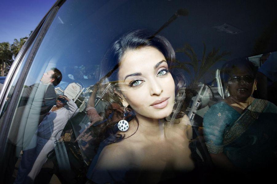 Aishwarya Rai en robe Armani et boucles d'oreilles De Grisogono assise à l'arrière d'une voiture Renault arrivant devant l'hôtel Martinez.