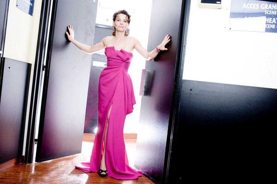 Juliette Binoche est en robe-bustier fuchsia en crêpe de soie de John Galliano pour Dior assortie à des bijoux vintage rubis et diamants de Bulgari dans l'entrebaillement d'une porte au Palais des Festivals